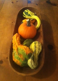 For this decoration, find a long wooden bowl and fill it with gourds or other seasonal items. Someday I would like to try getting a silver bowl and putting painted gourds in it!